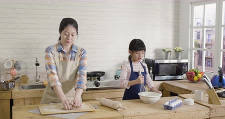 elegant asian mom and her children prepares pastry kneads dough on wooden counter with flour and rolling pin. Vídeos