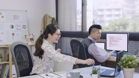 slow motion of young man coworker jump up celebrating successful by throwing document paper. two asian male and female colleagues with yes hand gesture yelling excited in office.