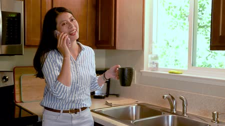 young asian pretty woman in kitchen standing by window with garden view talking on cellphone.