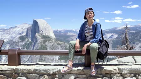 beautiful female hiker in cap relaxing in yosemite sightseeing looking around. Vídeos