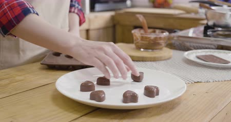female hands taking heart love chocolate out of flexible silicone mold putting on white plate dish on wooden table in kitchen.