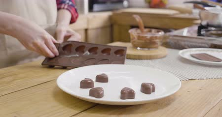 slow motion close up female hand take off chocolate in heart love shape from mold putting on white dish plate on wood table in kitchen.