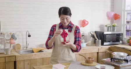 slow motion cute smiling young asian woman opening gift box in wooden modern kitchen on valentines day.