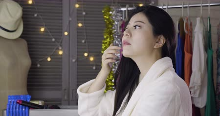 evsahibi : young beautiful asian japanese actress sitting in backstage looking at mirror doing makeup. girl in bathrobe get ready for show fixing hair in dressing room with sparkle light and clothes rack back