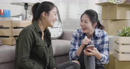 two asian family sisters moving apartment sitting on wood floor planning to redecorate new home.
