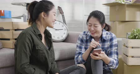 slow motion young girl friends sitting on floor of new house around cardboard boxes using smartphone smiling happy for new apartment. woman sharing mobile phone buying furniture online shop on sale.