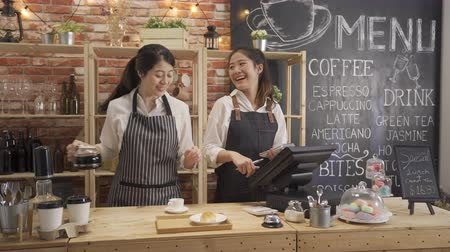 служить : two asian women in aprons laughing and standing behind counter while working in cozy small bakery together.