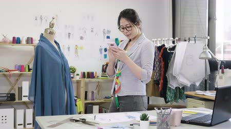 slow motion of young girl fashion designer enter information new collection in smartphone after measuring mannequin parts with tape-measure. Vídeos