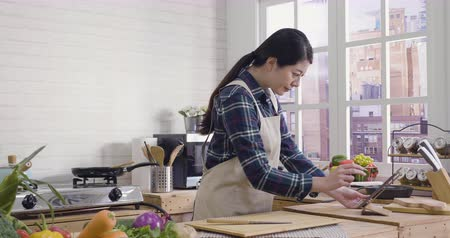 slow motion of happy young chinese woman in apron cooking at home. lunch preparation at modern kitchen. asian housewife checking recipe on internet in mobile touchpad with fresh vegetables on table