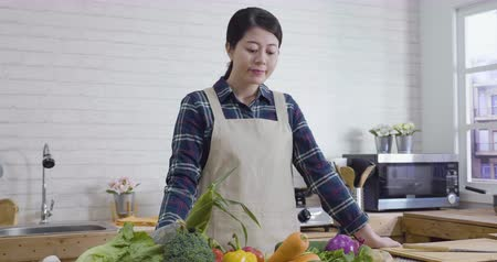 beautiful household woman in kitchen smiling looking at vegetables while double check ingredients and instructions on digital tablet.