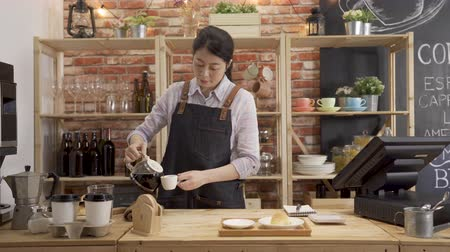 Professional barista woman preparing coffee alternative method. young girl bartender pour latte in cup and put on tray with croissant in counter. Vídeos