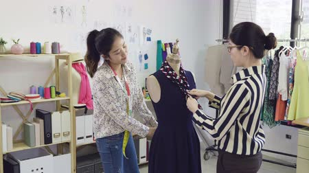 slow action beautiful fashion designer girls coworkers in studio near mannequin model and fix clothes together.