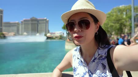 бульвар : Happy young modern woman tourist in sunglasses looking camera and talking on online video phone call in park. Стоковые видеозаписи