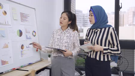 manager presents new project plan to malay woman colleague at meeting. Wideo