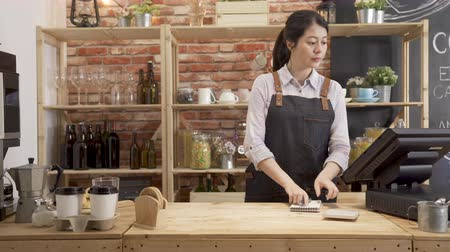 beautiful girl barista behind counter using tablet checking client order. Wideo
