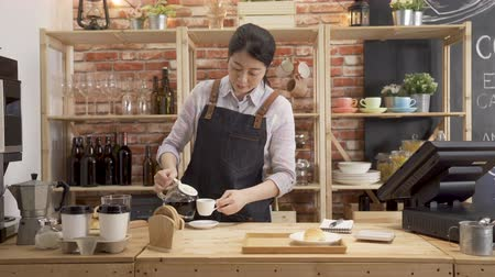 居酒屋 : young beautiful asian woman barista pour hot coffee in cup prepared for customer order in counter bar.