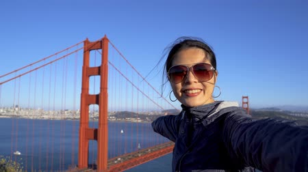 fast forward asian woman with sunglasses making video call waving hands showing friends the view of golden gate bridge in san francisco.