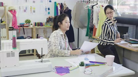 Fashion designer stylish showroom concept. two female dressmakers colleagues sitting at workplace drawing design on sketches.