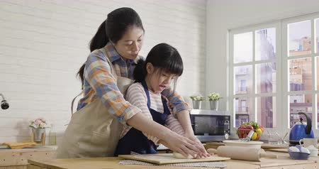 slow motion cute asian little girl and beautiful mother  flattening dough using hands at home kitchen prepare for happy mothers day cake.