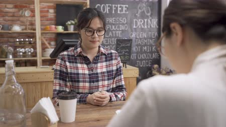 asian Japanese female job applicant arrive at interview gives resume to friendly hr recruiter in coffee shop. Vídeos