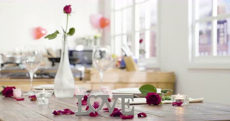 beautiful romantic wooden table set up ready with candles glass dish and flower vase for valentines day near window.