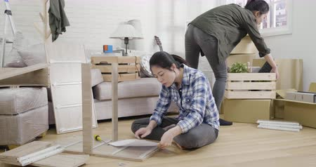 Young happy asian female friends renovating new house and moving furnishings together.