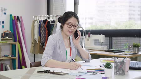dressmakers model : Professional fashion designer asian woman talking on mobile phone and drawing clothing sketch with pencil at table in tailoring shop.