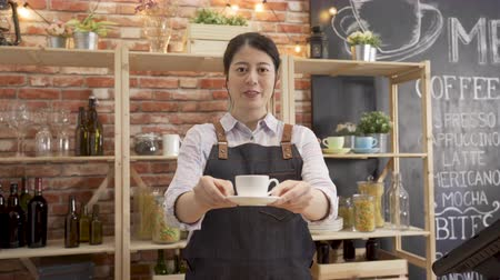 Coffee business concept. asian female barista serving cup of drink while standing in bar counter at cafe.