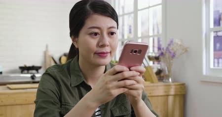 Young beautiful asian chinese woman using cellphone and having conversation online in modern kitchen.