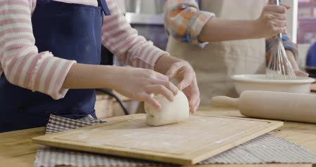 unrecognized young asian woman in apron holding bowl with dough and whisk in wooden kitchen house. little girl daughter standing beside kneading fresh dough for baking bread to mother