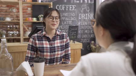 shy asian woman applicant give resume to interviewer, talking and drinking coffee with awkward smile.