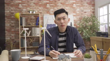 asian male architect with notebook studying plans in green office. Wideo