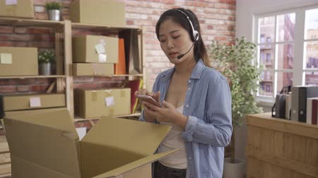 fast motion two female operator employee with headset against shelves with boxes in warehouse solve problem with client at online shop.