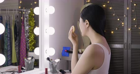 Woman applying makeup near mirror with light bulbs in dressing room. Wideo