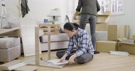 slow motion girl on floor reading instruction of diy wood product keep nodding head to understand procedure of assembly furniture.