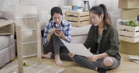 two elegant asian women read instructions for assembly furniture in new house with moving boxes on background.