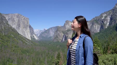 young beautiful asian woman hiker sightseeing tunnel view yosemite valley and bridalveil fall.
