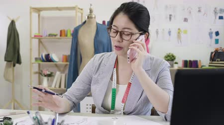 slow motion Beautiful asian woman fashion designer in glasses start up new small business in office chatting on smart phone while drawing sketch. Wideo