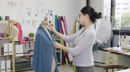 fashion clothing designer woman working with measurements mannequins in sewing studio.