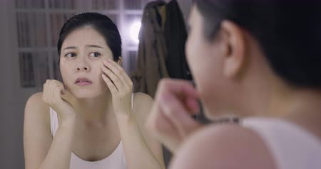 pěvec : slow motion asian woman entertainer looking on her face in mirror concern about skin problem.