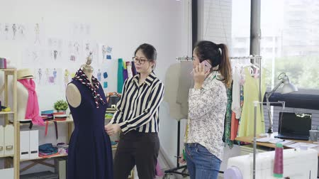 Smiling fashion designer woman talking on smartphone with customer in bright studio. Wideo