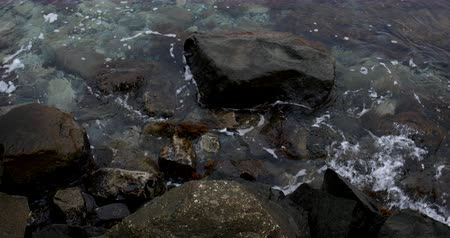 Sea waves at the rocky shore in overcast weather. Wideo