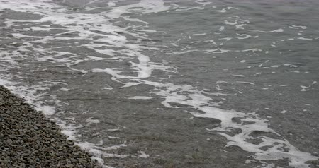 Sea waves at the rocky shore in overcast weather