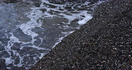Sea waves background at the rocky shore in overcast weather
