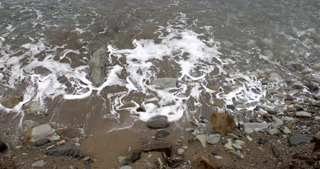 купание : Foaming and splashing background sea waves off a rocky shore in cloudy weather
