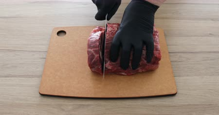 Cook in gloves cuts beef meat with a knife on a board and makes steaks ribeye Wideo