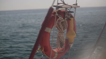 lifebelt : Red lifebuoy on the railing of the ship on the background of the sea Stock Footage