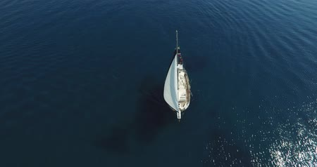 парусный спорт : Aerial view of a sail boat set sail on clear blue water in open sea