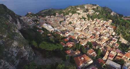 szicília : Aerial shot of the Taormina, ancient buildings and an amphitheater on the east coast of the island of Sicily, Italy Stock mozgókép