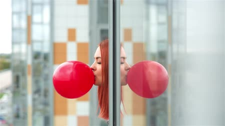 balonlar : Young beautiful red-haired girl inflates a red balloon leaning out of the windows of the building